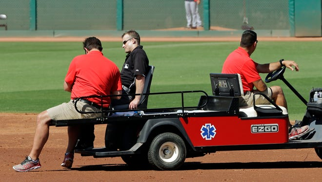 Umpire Brad Myers, second from left, is driven off the field after being hit by a line drive off the bat of Cincinnati Reds' Brandon Phillips in the second inning of a spring exhibition baseball game against the Cleveland Indians Monday.