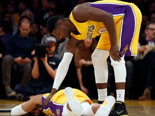 Los Angeles Lakers forward Julius Randle, right, checks on guard D'Angelo Russell, who fell to the floor with an injury during the first half of the team's NBA basketball game against the Indiana Pacers in Los Angeles, Friday, Jan. 20, 2017. (AP Photo/Alex Gallardo)
