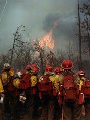 Hotshot crew members from Redmond, Ore., watch flames