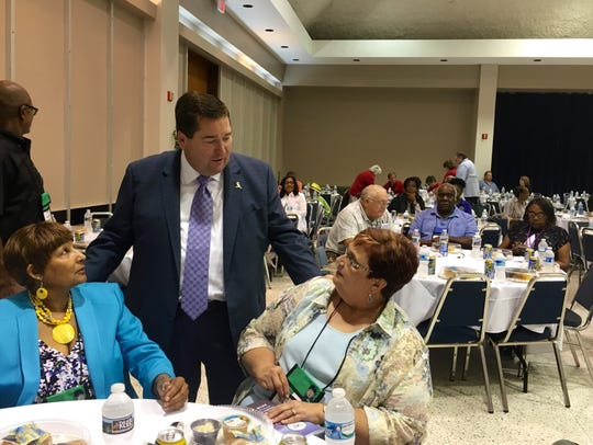 Lt. Gov. Billy Nungesser (center) talks with Village