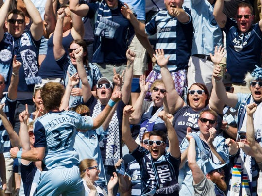 ADVNACE FOR WEEKEND EDITIONS, JULY 4-6 - FILE - In this May 4, 2014 file photo, Sporting Kansas City forward Jacob Peterson (37) celebrates with fans in the first half after he scored a goal against the Columbus Crew in an MLS soccer match in Kansas City, Kan. Major League Soccer is growing, with more lucrative TV and sponsorship deals and greater attendance. But it hasn't yet translated into a television ratings breakthrough, and the league hopes the World Cup provides a long-lasting boost.  (AP Photo/The Kansas City Star, Shane Keyser, File)