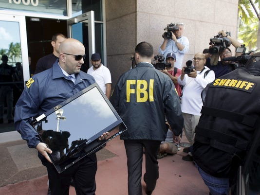 FBI agent brings out a computer after an operation inside the CONCACAF offices in Miami Beach, Florida