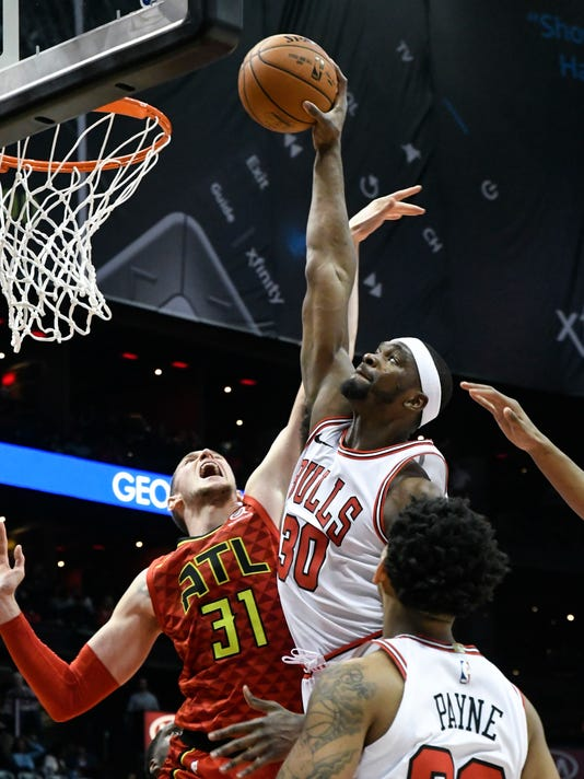 Chicago Bulls forward Noah Vonleh (30) shoots as Atlanta Hawks forward Mike Muscala (31) defends during the second half of an NBA basketball game Sunday, March 11, 2018, in Atlanta. Chicago won 129-122. (AP Photo/John Amis)