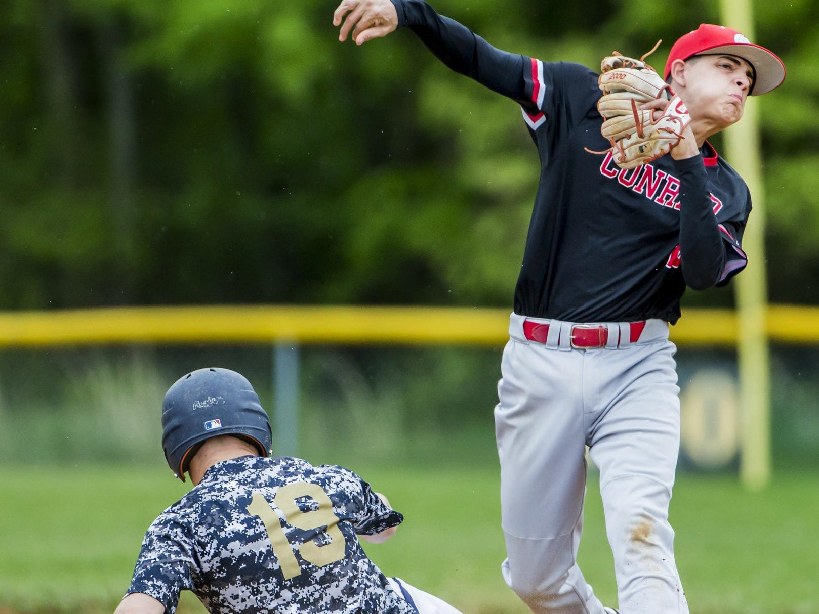 Conrad second baseman Kevin Russo throws to first as he tries to turn a double play after tagging out Delaware Military Academy's Jacob Hudson (No. 19) in Conrad's 1-0 win over Delaware Military Academy in Newark on Tuesday afternoon.