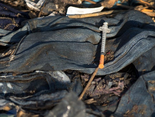 A used needle is abandoned amongst trash in a homeless camp in downtown Cincinnati.