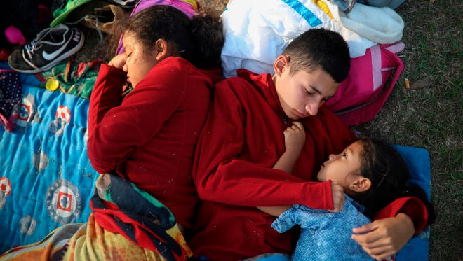 "In this April 4, 2018, photo, the Zelaya siblings, from El Salvador, Nayeli, right, Anderson, center, and Daniela, huddle together on a soccer field, at the sports club where Central American migrants traveling with the annual ""Stations of the Cross"" caravan are camped out, in Matias Romero, Oaxaca State, Mexico. The children's father, Elmer Zelaya, 38, said the family is awaiting temporary transit visas that would allow them to continue to the U.S. border, where they hope to request asylum and join relatives in New York."