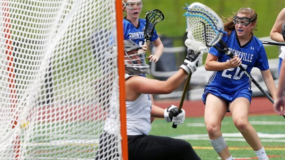 Bronxville's Isabel Sondey (20) scores past Millbrook goalie Claire Martell (30) during a 2018 girls lacrosse regional final at Newburgh Free Academy. Bronxville won 16-6.
