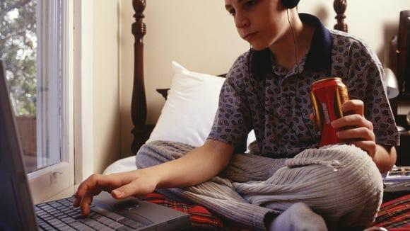 Teenage boy (16-17) using laptop, sitting on bed