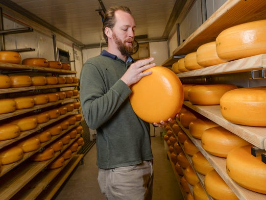 Don Lubsen flips a block of  gouda cheese aging in