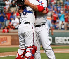 Texas Rangers starting pitcher Derek Holland (right) celebrates his complete game three-hit shutout