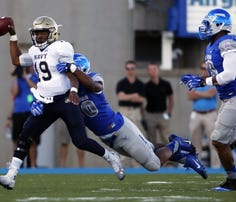 Navy's Keenan Reynolds, here being dragged down for a sack during last year's loss at Air Force, will have a chance for revenge Saturday in Annapolis.