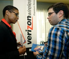 Sasha Vitalis, left, talks about job opportunities to job seeker Omar Delgado at a job fair in Miami Lakes, Fla., on July 15.