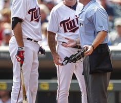 Minnesota Twins first baseman Joe Mauer (7) discusses the strikeout call of umpire Mike Muchlinski as manager Paul Molitor listens in the 1st inning at Target Field.