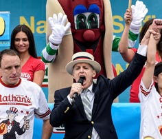 Mike Stonie defeats Joey Chestnut after eating 62 hot dogs at The Nathan's Famous Fourth of July International Hot Dog-Eating Contest in Coney Island, New York, on July 4, 2015.