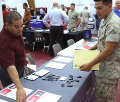A University of Phoenix liaison talks to a Marine at an education fair last year on Marine Corps Base 29 Palms, Calif. The Defense Department has suspended the for-profit school from recruiting on military bases.