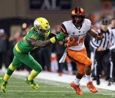 Nov 29, 2014; Corvallis, OR, USA; Oregon State Beavers running back Storm Woods (24) runs the ball in the second quarter as Oregon Ducks linebacker Torrodney Prevot (86) defends at Reser Stadium. Mandatory Credit: Scott Olmos-USA TODAY Sports