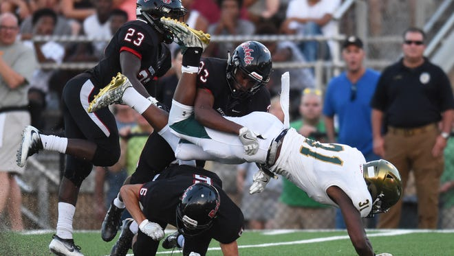 Maryville's Tommy Smith (23), Michael Buchanan (33) and Michael Jones (6) take down Catholic's Joshua Brown (31) during a high school football game at Maryville High School against Knoxville Catholic High School Friday, Aug. 18, 2017.