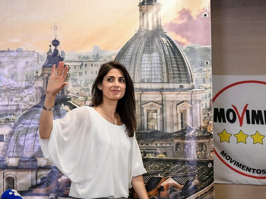 New Rome's Mayor Virginia Raggi of the 5-Star Movement waves at the end of a press conference in Rome, early Monday, June 20, 2016, soon after being elected. An anti-establishment newcomer, capitalizing on anger over political corruption and deteriorating city services, Raggi trounced Premier Matteo Renzi's candidate in Rome's mayoral runoff Sunday to become the first woman to head City Hall in the Italian capital. (Alessandro Di Meo/ANSA via AP)