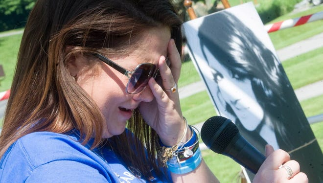Alyssa Fiorentino breaks down in tears as she attempts to read a poem about her sister, Brooke, seen in a photograph in the background, during a heroin awareness vigil at Kain Park in July 2015.