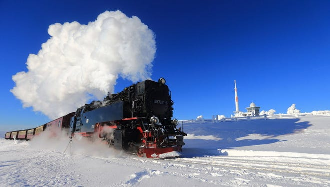 A steam-powered narrow-gauge railway locomotive pulls a passenger train on snow covered Brocken mountain in Wernigerode, Germany, Monday, Jan. 18, 2016.