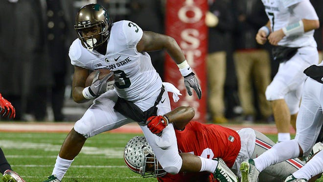 MSU running back LJ Scott drags a Buckeye tackler in the fourth quarter.