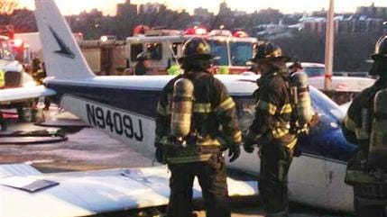 In this photo downloaded from the New York City Fire Department's Twitter account, firefighters stand near a light airplane that made an emergency landing on the Major Deegan Expressway in the Bronx borough of New York on Jan. 4, 2014.