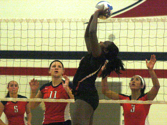 Churchill's Rayna Yetts delivers a set as John Glenn's (from left) Shelby Hodges, Carley Loving and Denae Tulo postion themselves on defense.