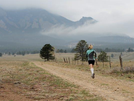 Woman Runner on Mountain Trail
