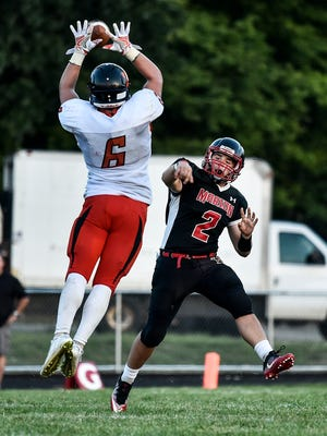 Mount Vernon's Andrew Crane attempts to block a pass from Marion Harding's Ryan Sayre during Friday's season opener at Harding Stadium. The Presidents return home Friday when they host Lima Senior at 7:30 p.m.