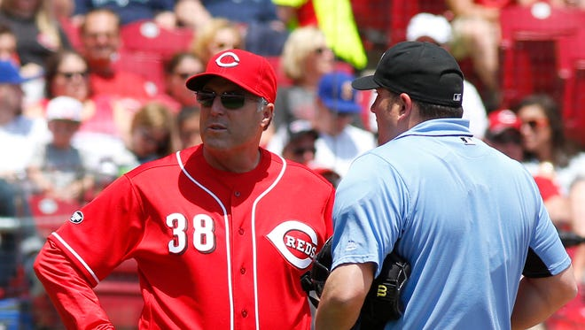 Reds manager Bryan Price talks with home plate umpire Dan Bellino during a break in the first inning of Sunday's loss to the Mariners.