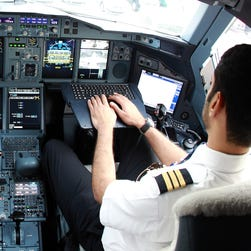 Pilots are shown in the cockpit of an Emirates Airbus A380.