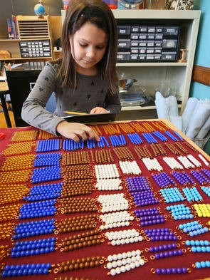 Isabella Martinez, 8, uses colored beads to visualize