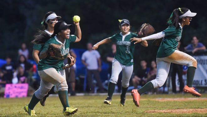The John F. Kennedy Islanders celebrate their Independent Interscholastic Athletic Association of Guam Girls Softball championship win against the Academy Cougars at Okkodo High School on March 22, 2017.