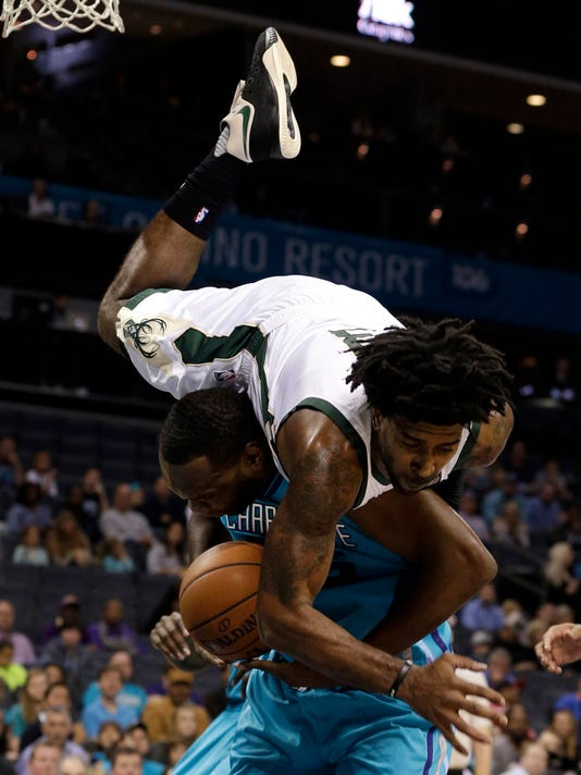 Milwaukee Bucks guard O.J. Mayo, top, flips over Charlotte Hornets center Al Jefferson in the first half of an NBA basketball game in Charlotte, N.C., Sunday, Nov. 29, 2015. Jefferson was fouled on the play. (AP Photo/Nell Redmond)
