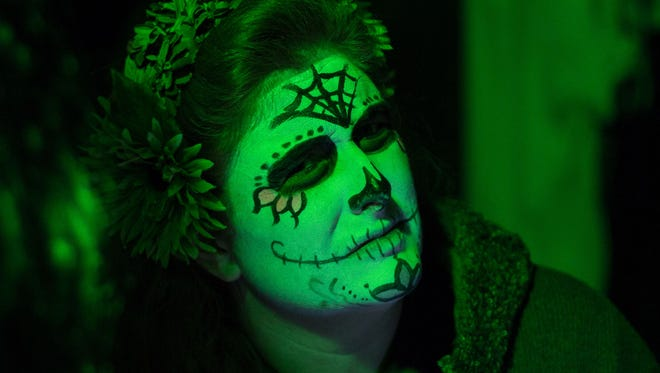 Painted as a skeleton Heidi Emmolas assigns groups at the Haunted Hallows on Saturday night.