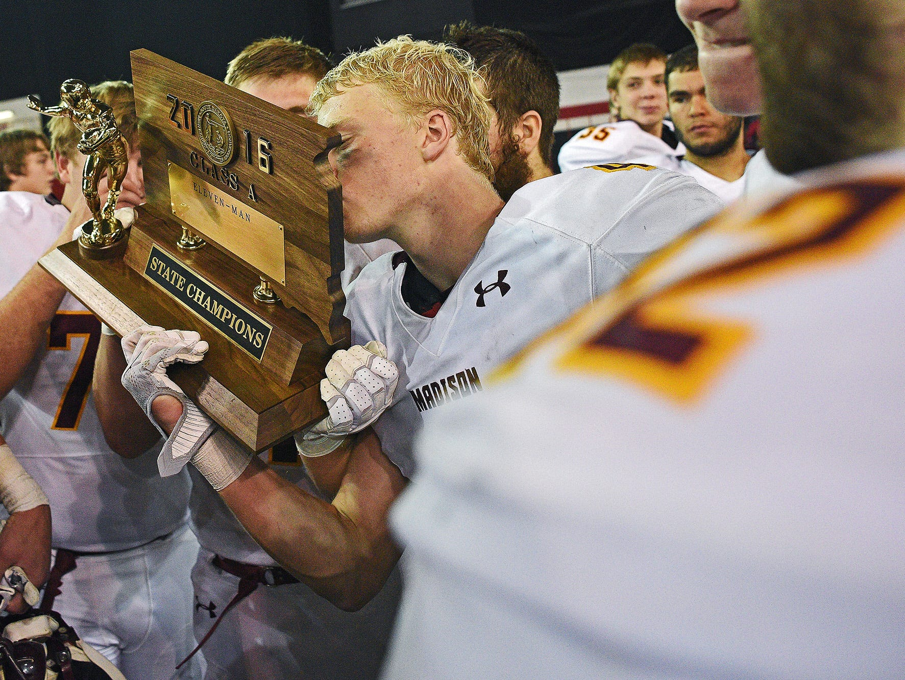 Madison's Mason Leighton (4) kisses their trophy while celebrating their 39-0 win over Tea Area with their fans and families after the 2016 South Dakota State Class 11A Football Championship game Saturday, Nov. 12, 2016, at the DakotaDome on the University of South Dakota campus in Vermillion, S.D.