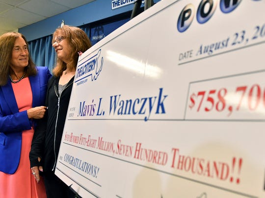 Mavis Wanczyk, of Chicopee, Mass., stands with state treasurer Deb Goldberg, left, during a news conference where she claimed the $758.7 million Powerball prize at Massachusetts State Lottery headquarters, Thursday, Aug. 24, 2017, in Braintree, Mass. Officials said it is the largest single-ticket Powerball prize in U.S. history. \(AP Photo/Josh Reynolds)