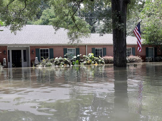 A United States flag hangs outside a flooded home in