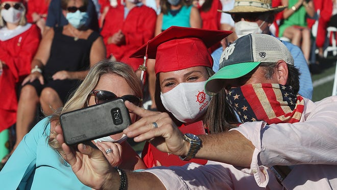 Olivia Brennan gets a selfie with her parents, Lisa and Dan, after receiving her diploma from Hingham High on Saturday, Aug. 1, 2020.
