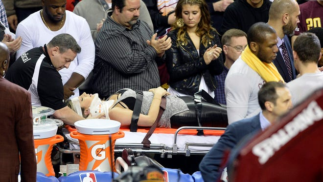 Ellie Day, wife of golfer Jason Day (not pictured), leaves the arena on a stretcher after she was run into by Cleveland Cavaliers forward LeBron James (not pictured) while she sat in the front row during a game between the Cleveland Cavaliers and the Oklahoma City Thunder at Quicken Loans Arena.