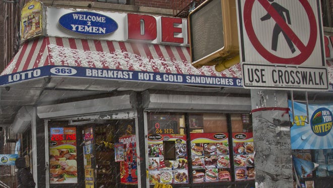 A woman approaches a deli where a robbery occurred, shortly before police and suspects exchanged shots, Jan. 6, 2015, in New York. Two NYPD officers from Rockland were injured.