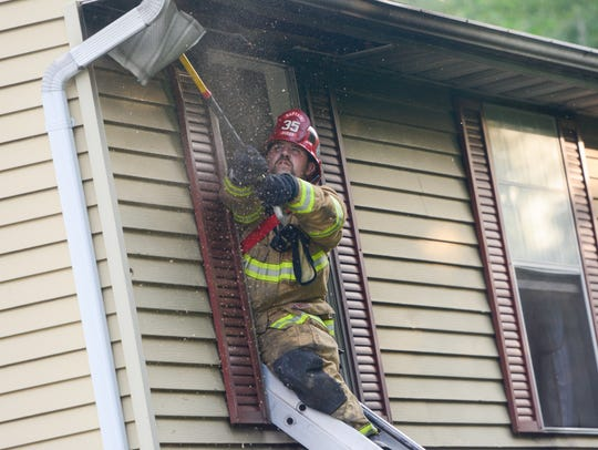 A fire fighter pulls the soffit out to check for hot