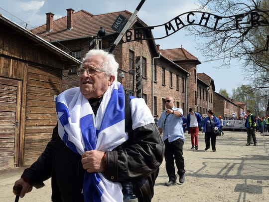An elderly man passes the main gate of the former Nazi