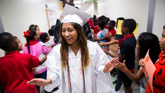 Stephanie Palacios, 18, receives high-fives as she makes her way down the hallway on Thursday, May 25, 2017 at Parkside Elementary School. Graduating seniors from Lely High School returned to walk the halls to show Parkside Elementary School students how far they've come. Palancios will be attending Florida Gulf Coast University in the fall.