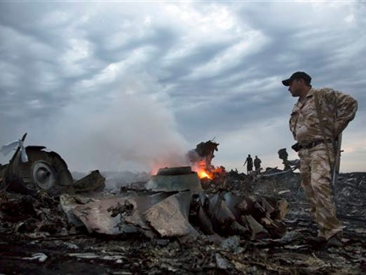 In this July 17, 2014, file photo, people walk amongst the debris, at the crash site of a passenger plane near the village of Hrabove, Ukraine. More travelers are flying than ever before, creating a daunting challenge for airlines: continue to keep passengers safe in an ever more crowded airspace.  Last year, 3.1 billion passengers flew, twice the total in 1999. Yet, the chances of dying in a plane crash were much lower.