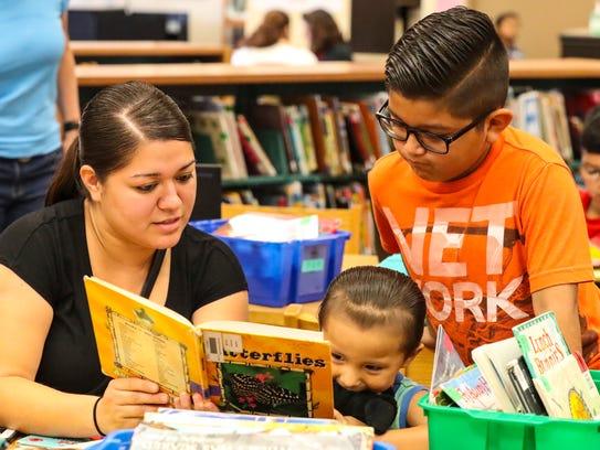 Heidy Gaona reads her youngest son Kayden Hernandez