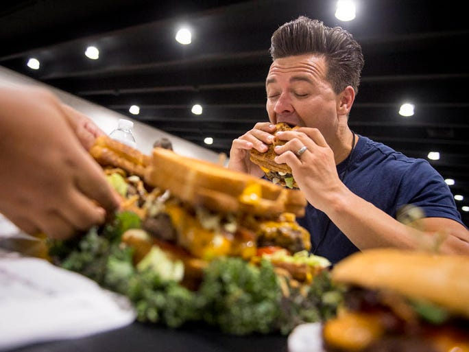 August 28, 2016 - Judge Dustin Starr takes a bite of the 'Fatty Melt' burger made with a dry-aged beef patty, jalepeno cream cheese, cheddar, bacon, fried onion straws and garlic cilantro lime sauce with two grilled cheese sandwiches serving as the bun during judging for the Best Memphis Burger Fest inside the Pipkin Building at Tiger Lane. The annual event benefits Memphis Paws, Inc., a non-profit group supporting responsible pet ownership and animal rescue organizations. Dozens of teams competed in the event which offered samples of sliders to attendees, live music, food trucks, a kids entertainment area and cornhole tournament.