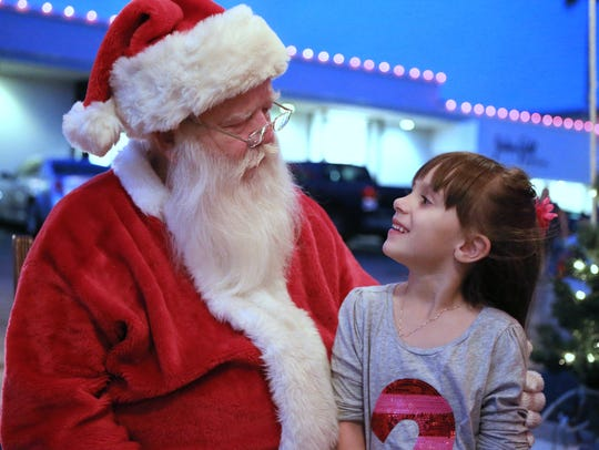 Lyla Cantu, 6, talks with Santa after taking pictures