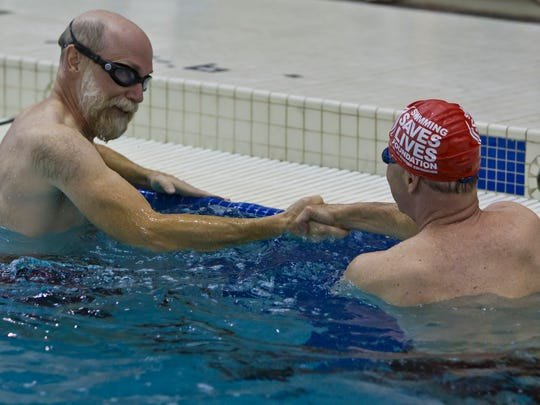 Kevin Johnston of West Lafayette shakes the hand of Purdue University President Mitch Daniels after they both swam a lap March 31, 2014, at the Boilermaker Aquatic Center in West Lafayette, Ind.