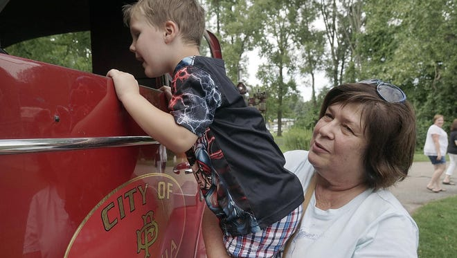 Four-year-old Keaton Zawacki attended the Fire Department's anniversary celebration with grandparents Sue and Garry Zawacki. Grandma Sue gives him a boost so he can look inside the cab of the antique fire truck.